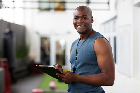 handsome african american male trainer with clipboard Stock Photo