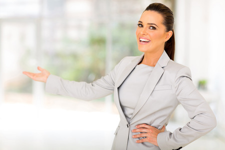 welcome smile: friendly businesswoman doing welcoming gesture