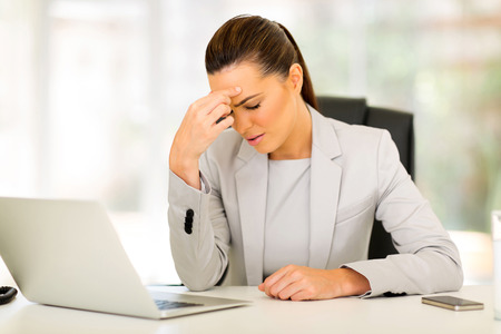 woman headache: young businesswoman having headache at work