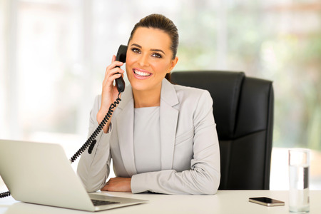 beautiful young businesswoman talking on landline phone Stock Photo