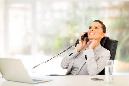 mujer trabajadora: relajada empresaria utilizando el tel�fono en oficina