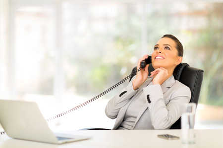 charming business lady: relaxed businesswoman using telephone in office Stock Photo