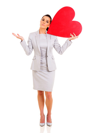 clueless: confused businesswoman holding red heart symbol on white background