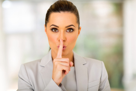 pretty young businesswoman saying shhh