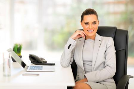カメラを見て事務所の魅力的な若い女性実業家
