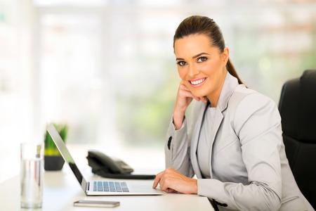 sourire, femme affaires, portable utilisation, ordinateur portable