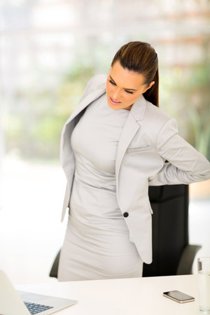 back to work: young businesswoman having lower back pain in office Stock Photo
