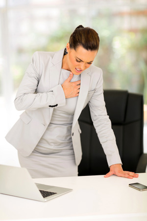 unease: young businesswoman having heart attack or chest pain Stock Photo