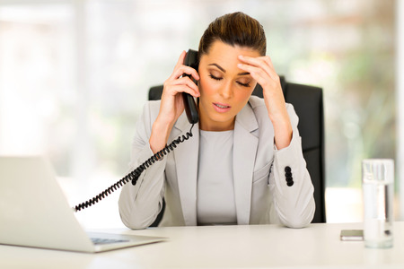 business woman phone: stressed businesswoman talking on telephone in office Stock Photo