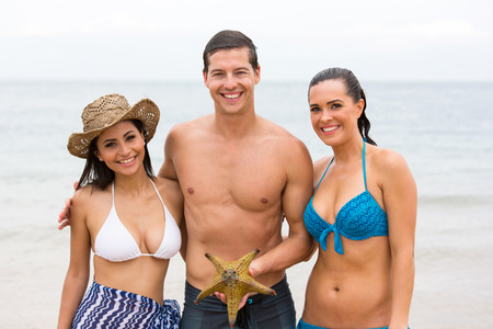 group of happy friends with starfish at the beach photo