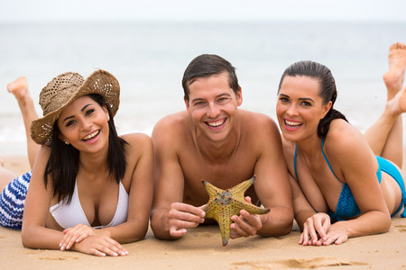 happy three friends lying on beach sand and holding a starfish photo