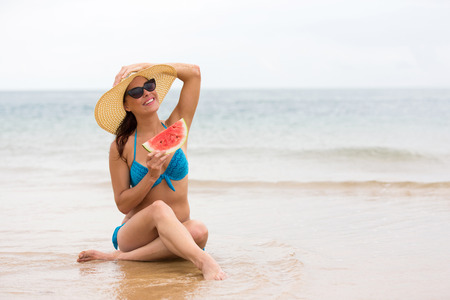 one piece: beautiful young woman holding a piece of watermelon on beach