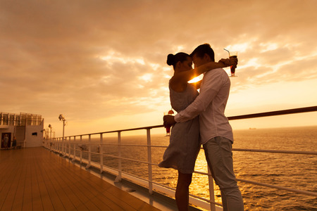 romantic couple hugging with eyes closed at sunset on a cruise ship