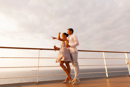 adult cruise: lovely young couple pointing at sea on a cruise ship at sunset