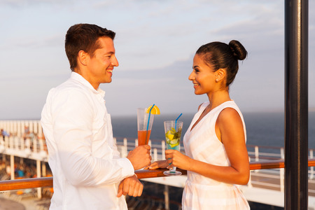 alcohol drinks: beautiful young couple on a date having drinks on a cruise ship Stock Photo