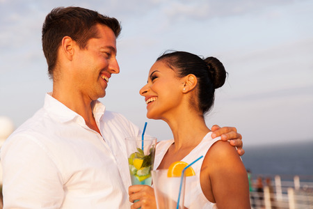 man relax: romantic young couple on cruise having cocktails