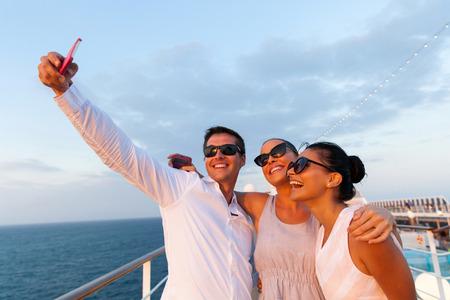 bateau voile: groupe d'amis qui prennent autoportrait en utilisant téléphone intelligent sur la croisière