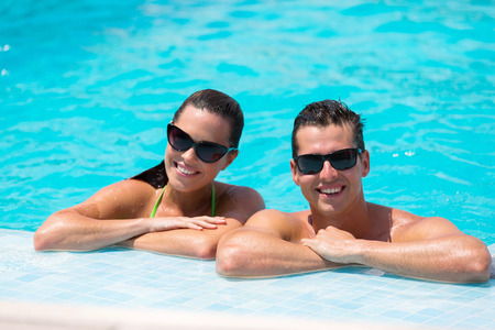 wife of bath: smiling young couple leaning on poolside Stock Photo