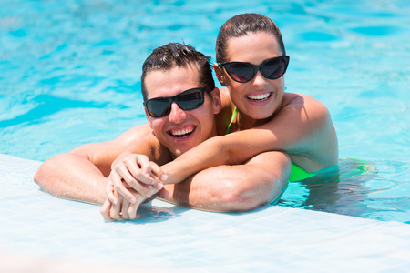 lovely women: portrait of cheerful young couple in swimming pool