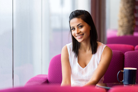 woman looking: happy young woman sitting in cafe