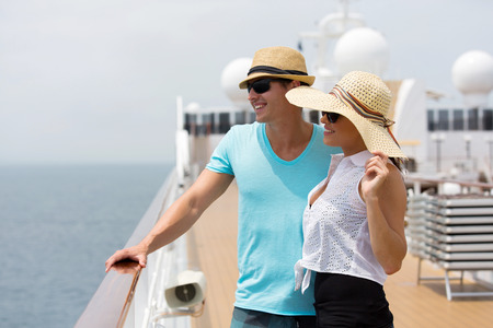 adult cruise: cheerful young couple looking at sea view on cruise ship
