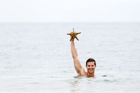 sea sexy: happy young man in ocean showing a starfish
