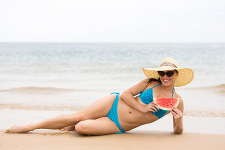 girl in bikini with watermelon on the beach photo