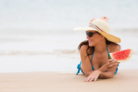 one piece: pretty woman with a piece of watermelon at the seashore Stock Photo
