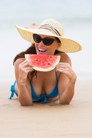 cheerful young woman eating watermelon on beach photo