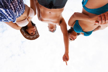 low angle view: low angle view of friends in swimsuits pointing