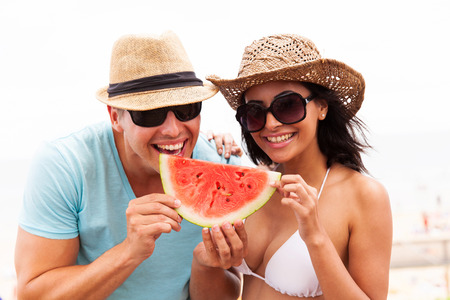 playful young couple with slice of watermelon on summer holiday photo