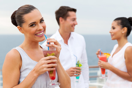 pretty woman drinking tropical juice with friends on background photo