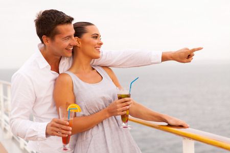 adult cruise: cheerful couple with cocktails enjoying sea view from cruise ship
