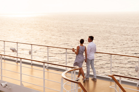 cute couple walking on cruise ship deck at sunset