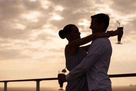 silhouette of lovely couple hugging at sunset on a cruise ship