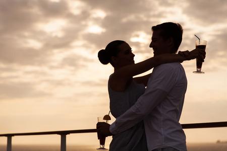 romantic couples: silueta de pareja encantadora abrazando al atardecer en un crucero