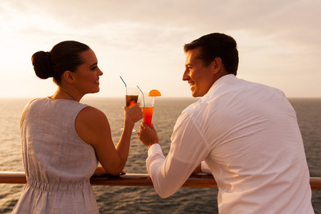 ship deck: romantic young couple toasting with cocktail on cruise ship
