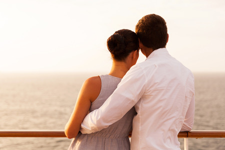 man rear view: rear view of young couple on cruise vacation looking at the sea