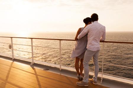 クルーズ船で夕暮れを抱いて若いカップルの背面図
