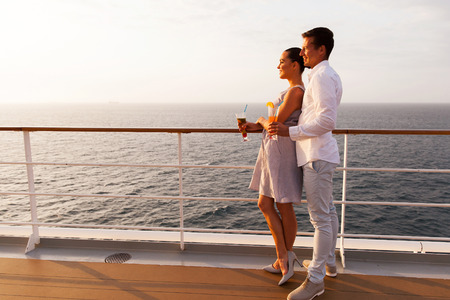 adult cruise: side view of smiling couple having cocktails on cruise ship at sunset
