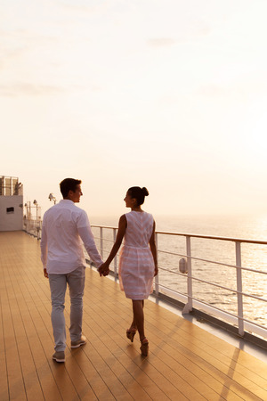 adult cruise: rear view of couple holding hands walking on cruise ship