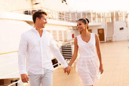 couple holding hands: cheerful young couple walking on cruise ship