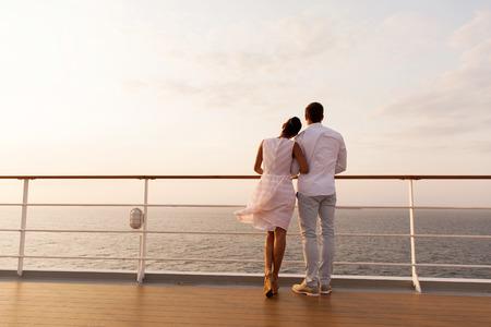 vista trasera de la joven pareja de pie en la cubierta del barco durante la puesta de sol Foto de archivo