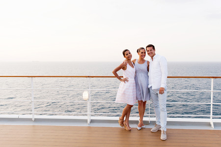 cruise travel: full length portrait of three friends standing on cruise ship deck Stock Photo