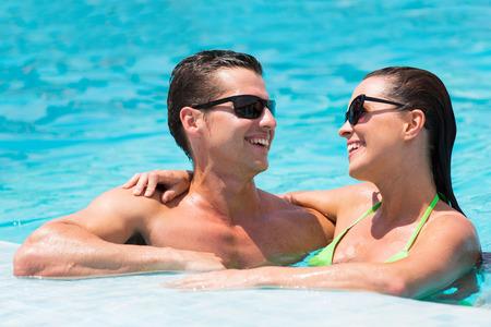 joyful couple having fun in swimming pool photo