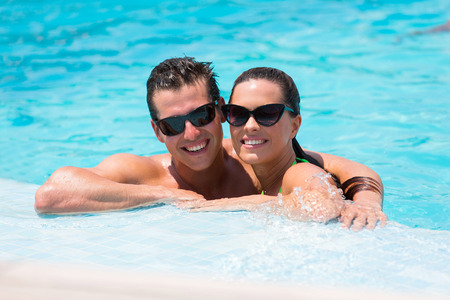 happy couple relaxing on the edge of swimming pool photo