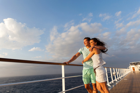 lovely women: loving married couple standing on cruise deck enjoying sunset together