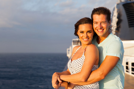 lovely couple: happy young couple looking at the camera on a cruise ship