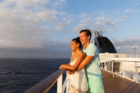 adult cruise: cheerful young couple looking at sunrise on cruise ship