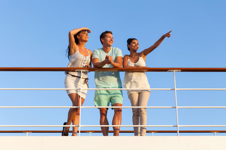 group of cheerful friends enjoying sunset on cruise Stock Photo